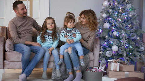 Happy family at Christmas, mum, dad and two little girls sitting at home on the Footage