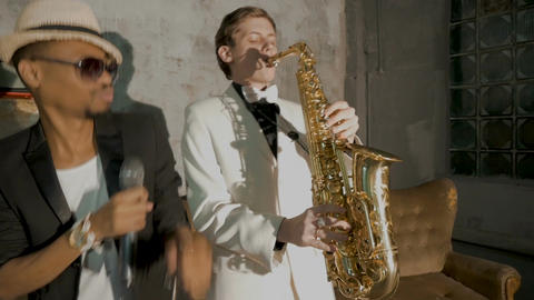 Two musicians show the performance. An African man is singing, a white man is Footage