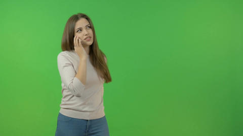 A white girl with long hair talks on a smartphone. On the green screen Footage