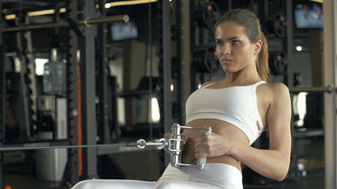 Strong woman lifting weights on training equipment in fitness club Footage