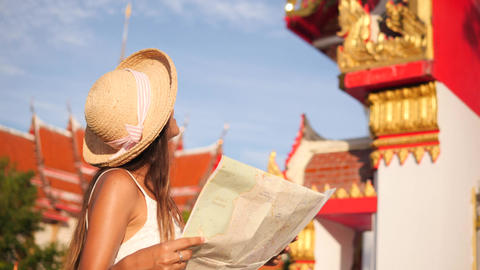 Young Hipster Tourist Girl with Map Exploring Traditional Thai Buddhist Temple Footage