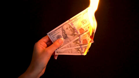 Burning dollars in a hand close-up on a black background. Slow motion Filmmaterial