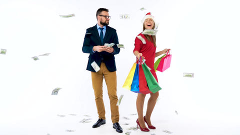 Dollars falling on formally dressed man and woman in the Santa Claus hat. Let's Footage