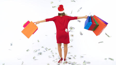 Dollar bills falling on Christmas shopping woman with multicolored shopping bags Footage