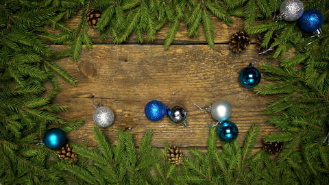 Christmas decorations falling on a wooden background with fir branches and cones ビデオ