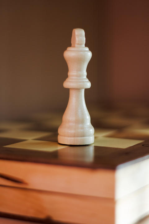 White Queen chess piece on chess board Photo