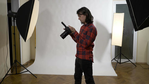 Young attractive white male photographer sitting in his photo studio checking Footage