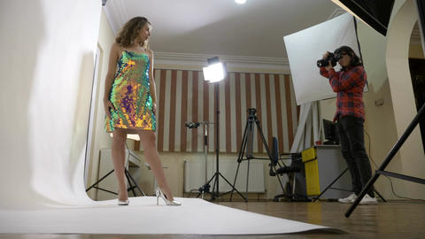 Young woman wearing a sparkly dress being photographed by her husband in an Footage