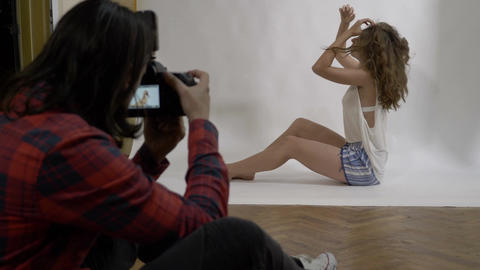 Attractive sexy teenager posing sitting on the floor dressed in pajamas in a Footage