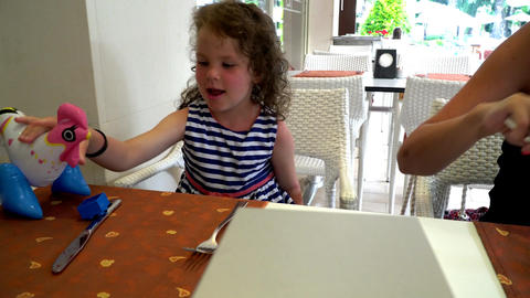little girl playing at the table with an inflatable cock Footage
