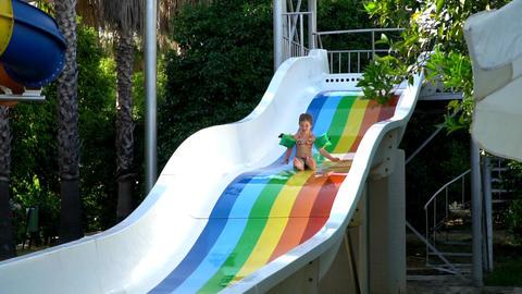 A little girl slips on a water slide Footage