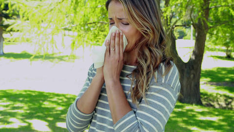 Woman blowing nose with tissue paper Live Action