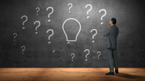 Businessman looking at question marks and bulb Footage