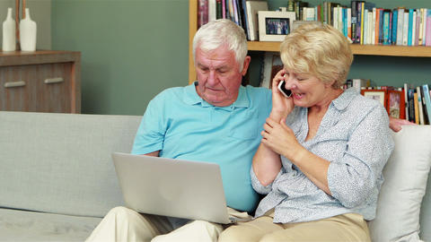 Senior couple using laptop and smartphone Footage