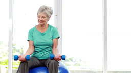 Senior woman sitting on exercise ball Live Action