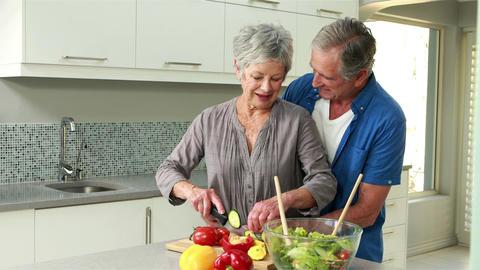 Happy senior couple making a salad Footage