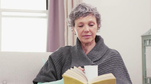 Concentrated woman reading a book while drinking coffee Footage