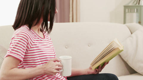 Smiling brunette reading a book while drinking a coffee Footage