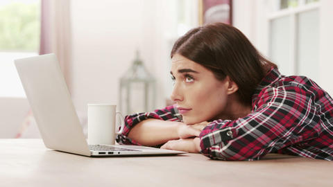 Exhausted woman using laptop while drinking coffee Footage