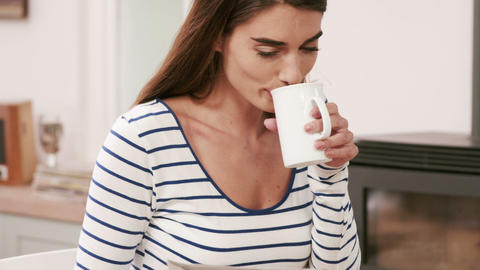 Pretty brunette reading newspaper while drinking coffee Footage