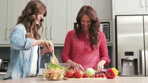 Two female friends preparing vegetables Footage