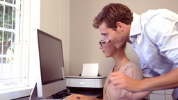 Serious woman working on computer while man showing a file Footage