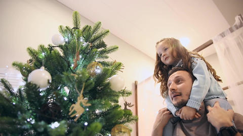Girl sits at daddy on the neck and they decorate the Christmas tree Live Action