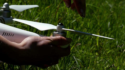 A modern quadracopter is fixed with male hands in summer Filmmaterial