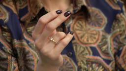 The hand of a girl with a manicure and a ring is touching Filmmaterial