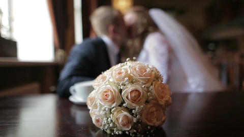 Blurred couple of newlyweds kissing while sitting in cafe. a bouquet of the Footage