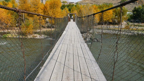 POV video of walking through old shaky suspension bridge Footage
