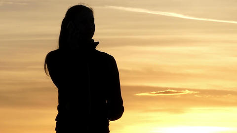 A beautiful pregnant woman calls her friend at sunset in slo-mo Footage