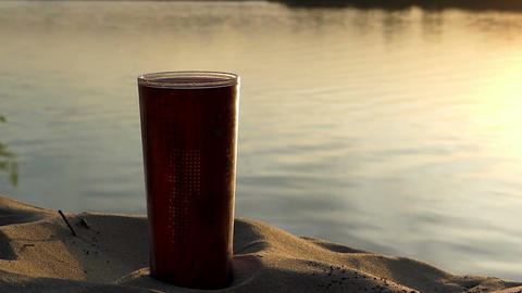 A plastic cup of coffee on a lake bank at a nice sunset in summer Footage