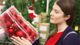 Woman buying Christmas decorations. Female choosing Christmas balls. Christmas Footage