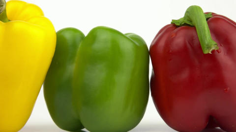 Movement of the camera along three different colored peppers Footage