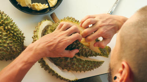 Young Tourist Man Peeling Exotic Ripe Durian Montong Thai Fruit with Knife Footage