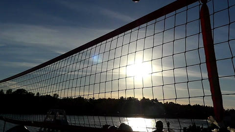 Amateur men playing volleyball at a network at sunset in slow motion Footage