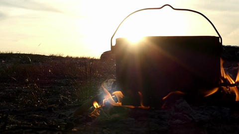 Black cauldron stands in a campfire. It boils hot water at sunset in slow motion Footage