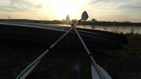 Two oars lie on a catamaran boat on a lake bank at sunset ビデオ