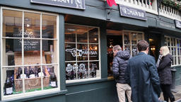 Traditional English pub with customers ordering drinks through an open window 画像