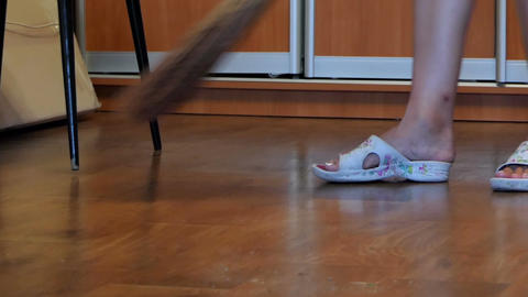 Female Legs And a Broom Sweeping Floor Footage