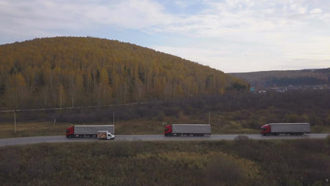 Freight trucks and cars moving on suburban road on background autumn forest Footage