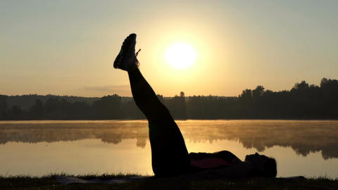 Woman lies on her back and trains her belly at sunset 画像