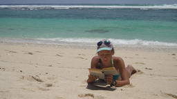 Girl on the beach reading a book ビデオ