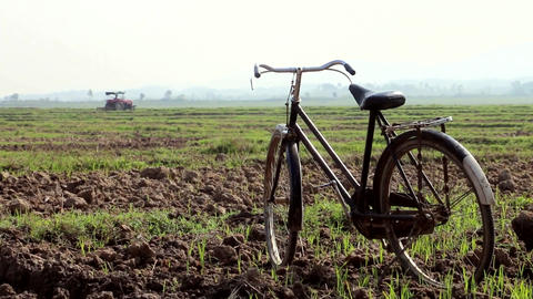 Old Bicycle On The Field With Distant Tractor Footage