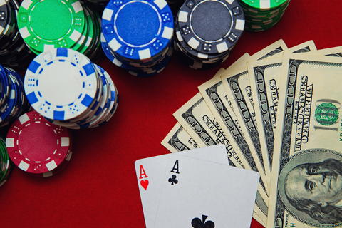 Pair of aces with dollars and poker chips Photo