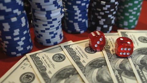 Red dice falling on money, gambler playing game at casino, addiction to gambling 画像