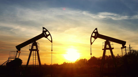 working oil pumps silhouette against sunset Footage