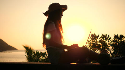 Young Mixed Race Freelancer Girl Working on Laptop with Beautiful Beach Sunset Footage