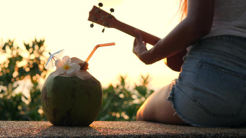 Young Hippie Girl Playing Ukulele Guitar at Beautiful Tropical Beach Sunset. 4K ビデオ